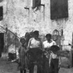 Foto antiga de la masia de Can Banús, on s'aprecia la porta adovellada a la dreta (dècada de 1910-1920)